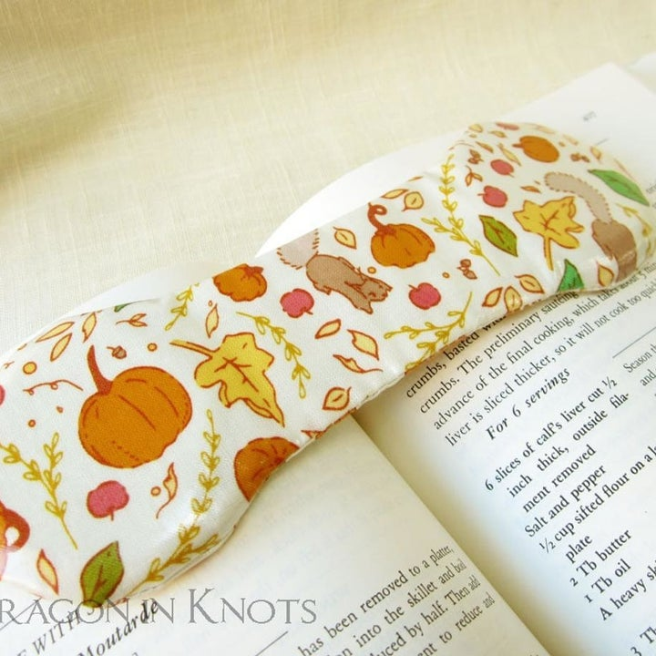 A smaller book weight with a fall pattern of pumpkins, leaves, and squirrels on it