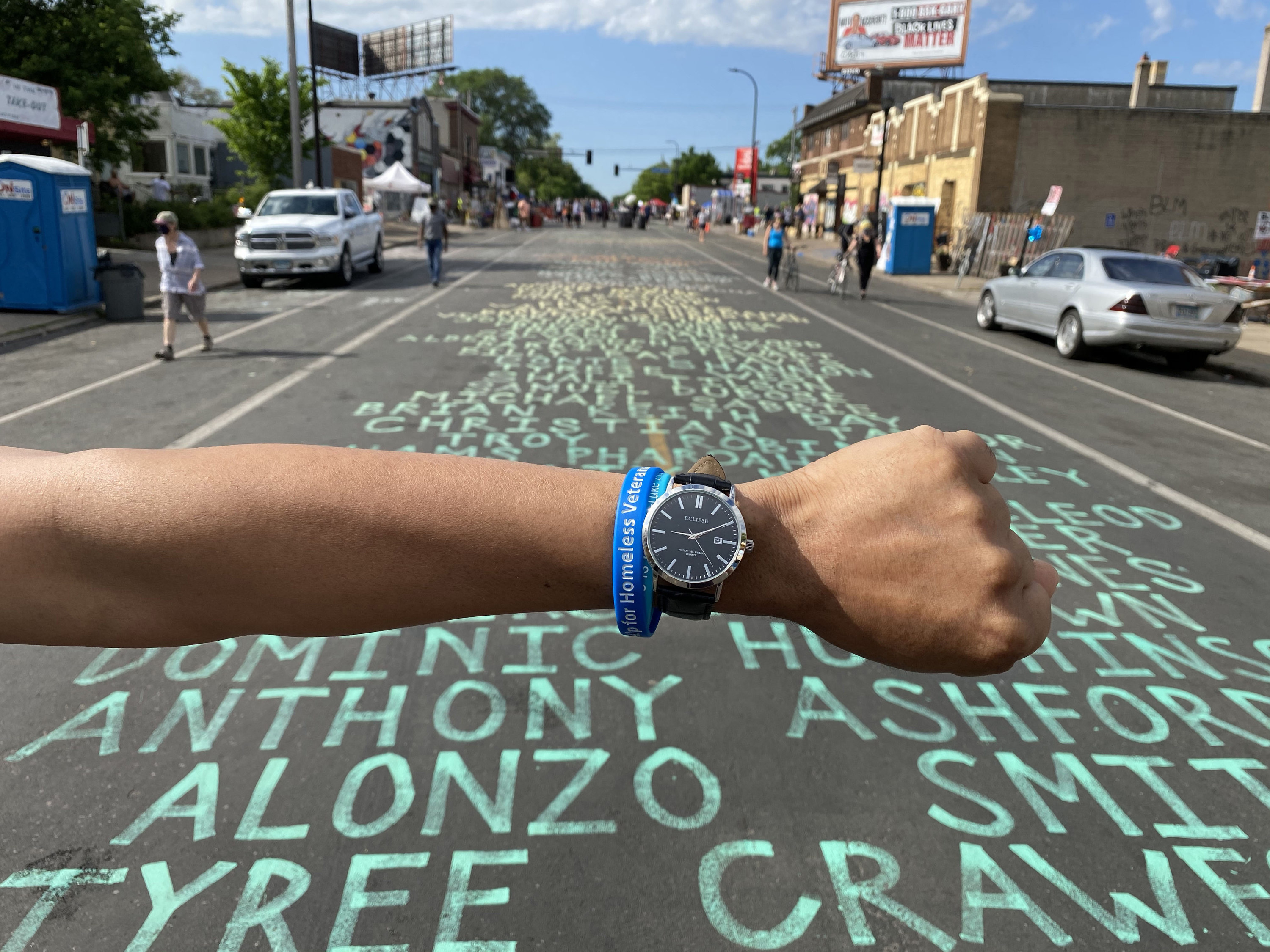An arm wearing a watch in front of a list of names written in chalk on the street
