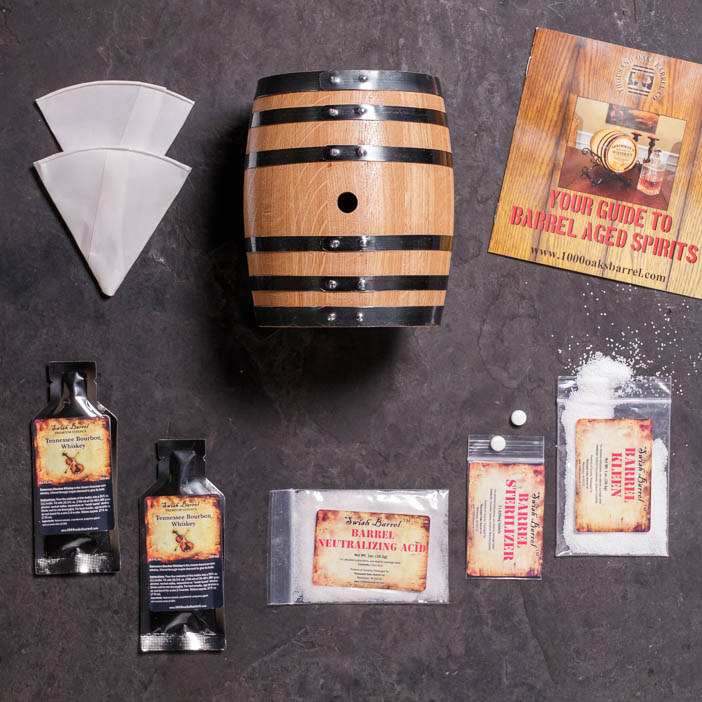 The barrel of a whiskey making kit displayed alongside all of the necessary ingredients and an instruction pamphlet