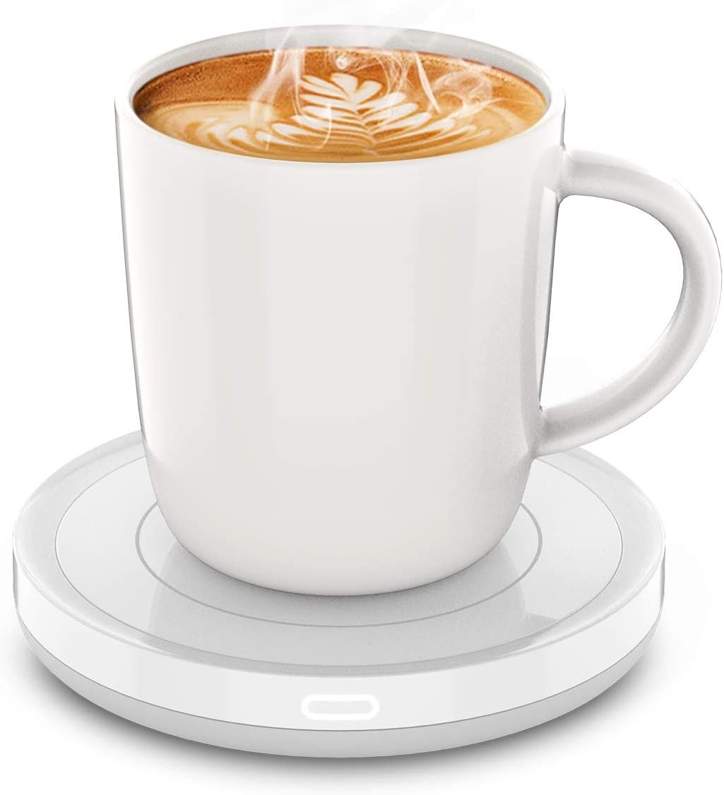 A steaming mug on a small white warming base