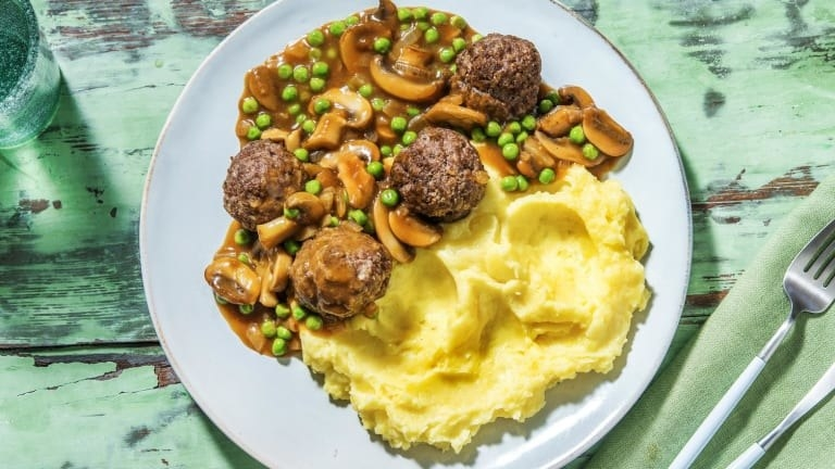 Salisbury steak potatoes with mushrooms and peas in gravy and smashed potatoes