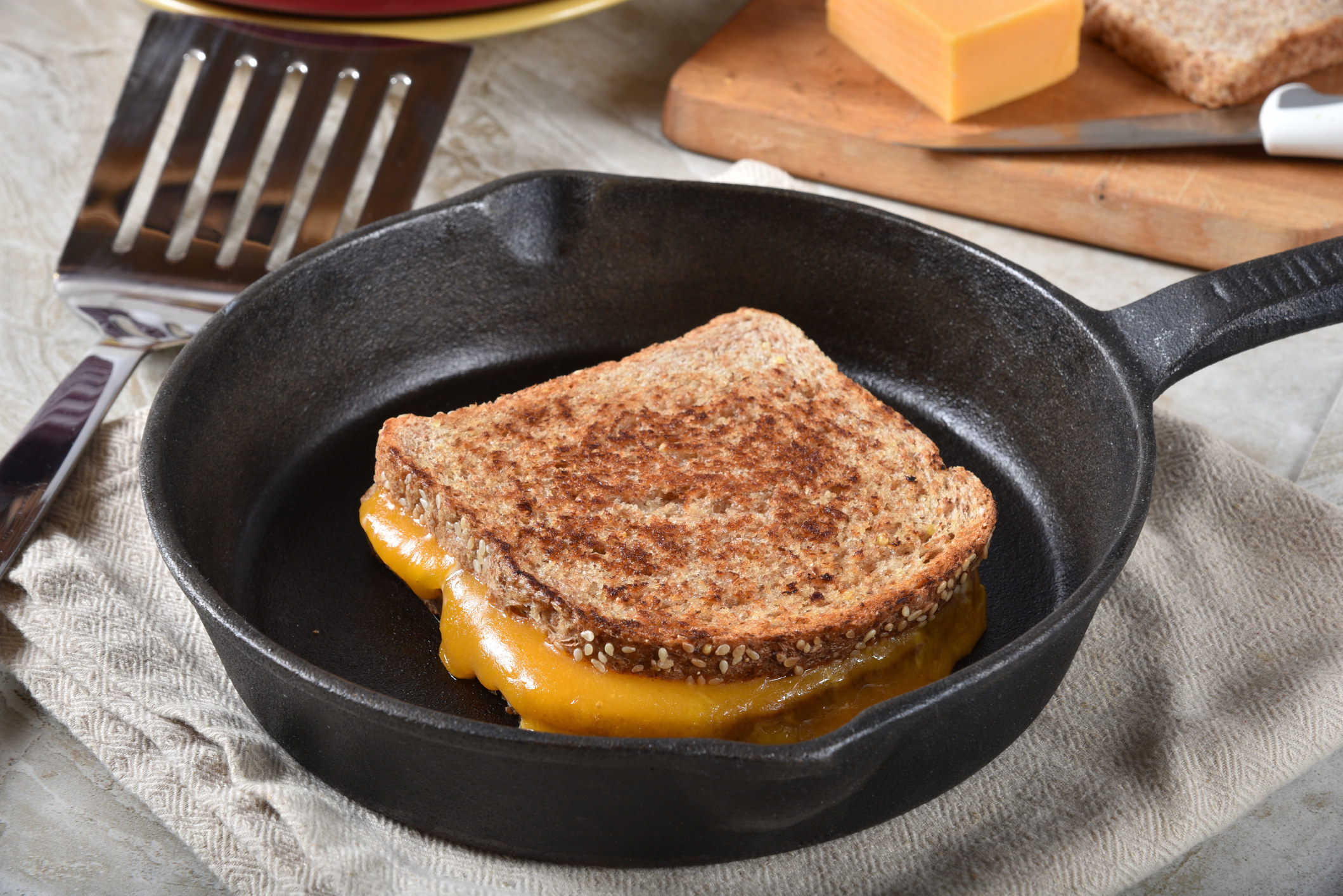 A grilled cheese sandwich on sprouted multi-grain bread in a cast iron skillet