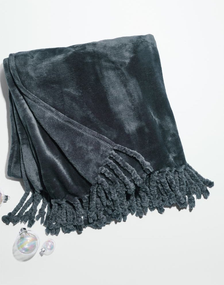 The velvet blanket in blue with fringe on the ends