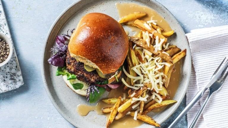 Un hamburger avec des frites recouvertes de sauce et de mozzarella