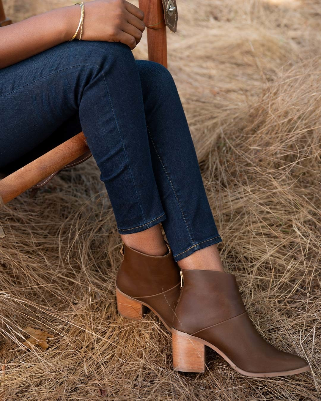 A model in brown stacked heel ankle boots