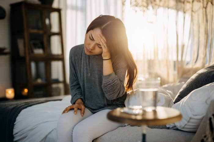 Woman sitting on bed holding her head.