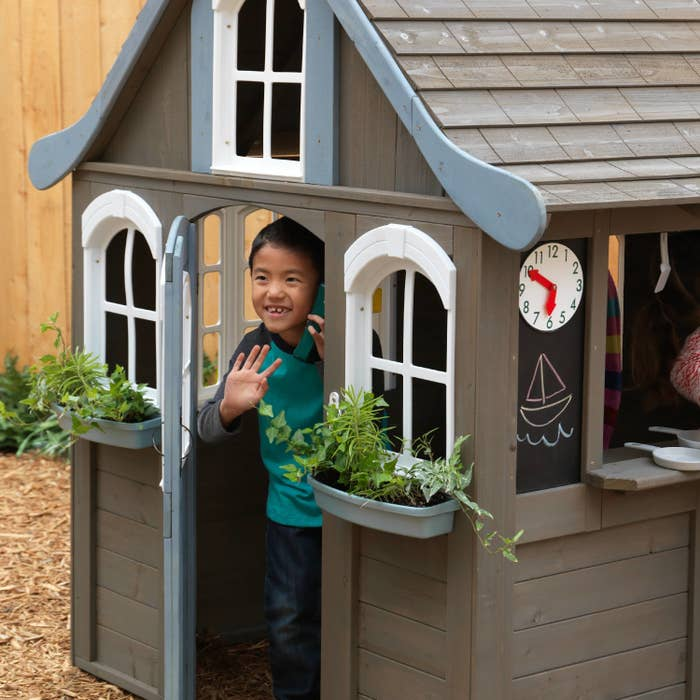 child waving while inside a playhouse