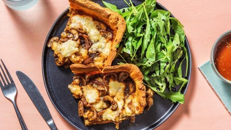 La pizza épaisse aux champignons et au mozzarella avec une salade de roquette