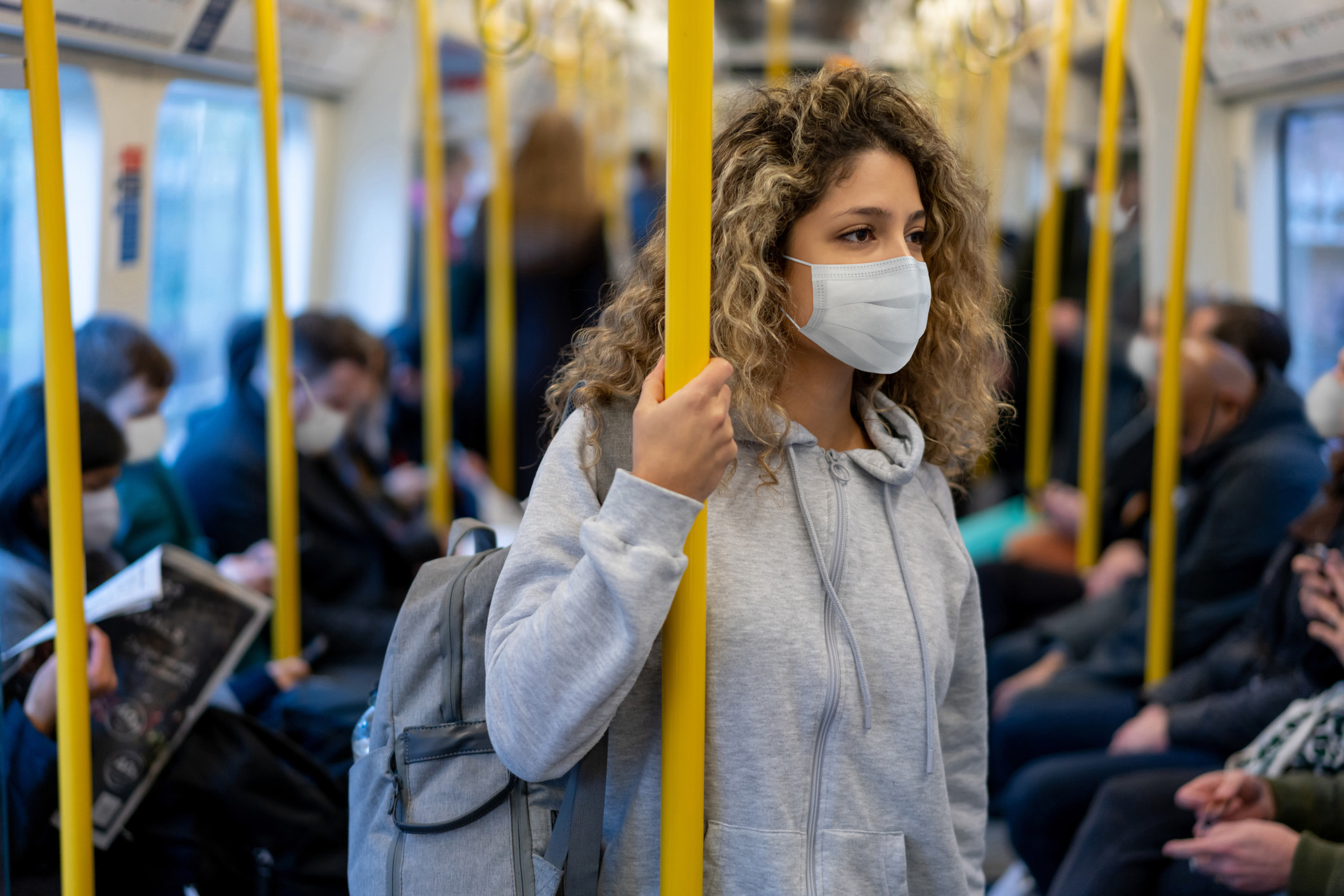 Beautiful young woman riding on the metro wearing a facemask to avoid an infectious disease - COVID-19 lifestyle concepts