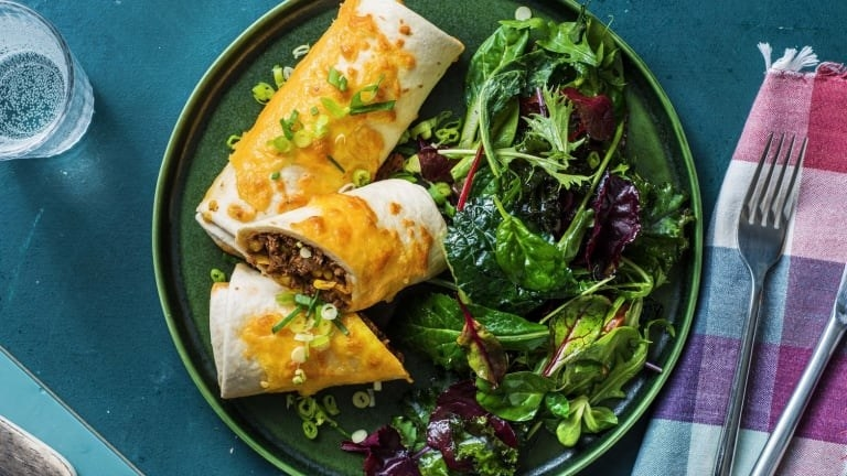 Chimichangas au bœuf et au maïs recouverts de queso avec une salade d'accompagnement