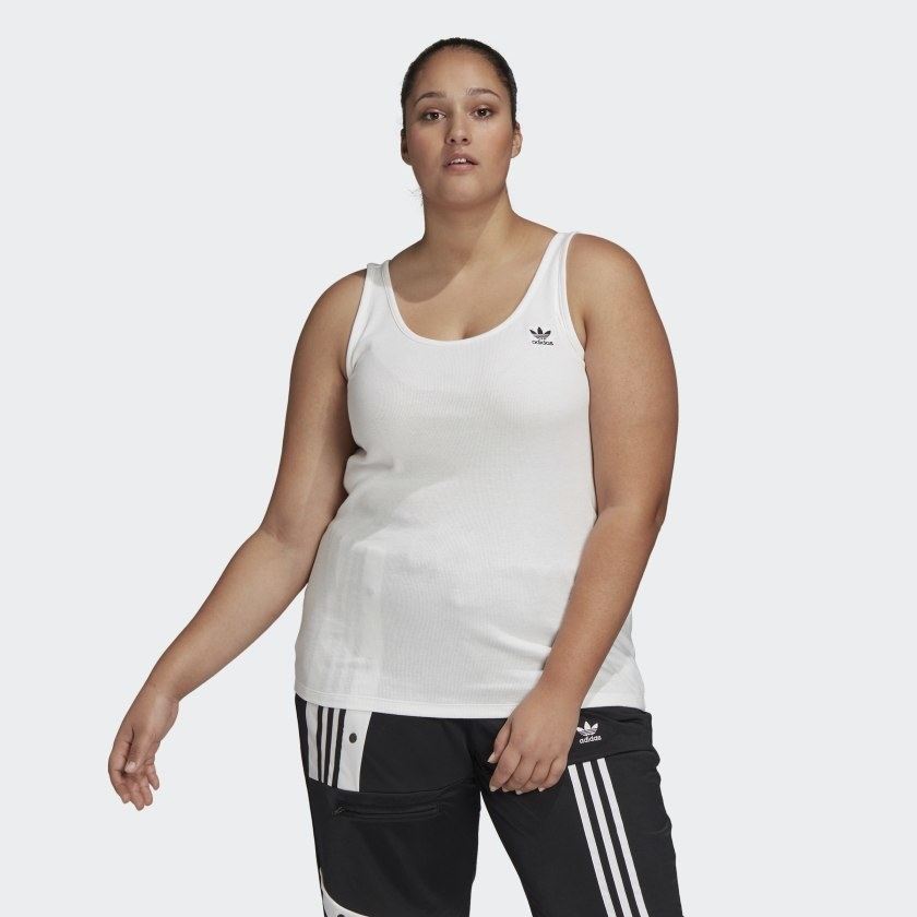 Model wears basic white workout tank with Adidas striped track pants