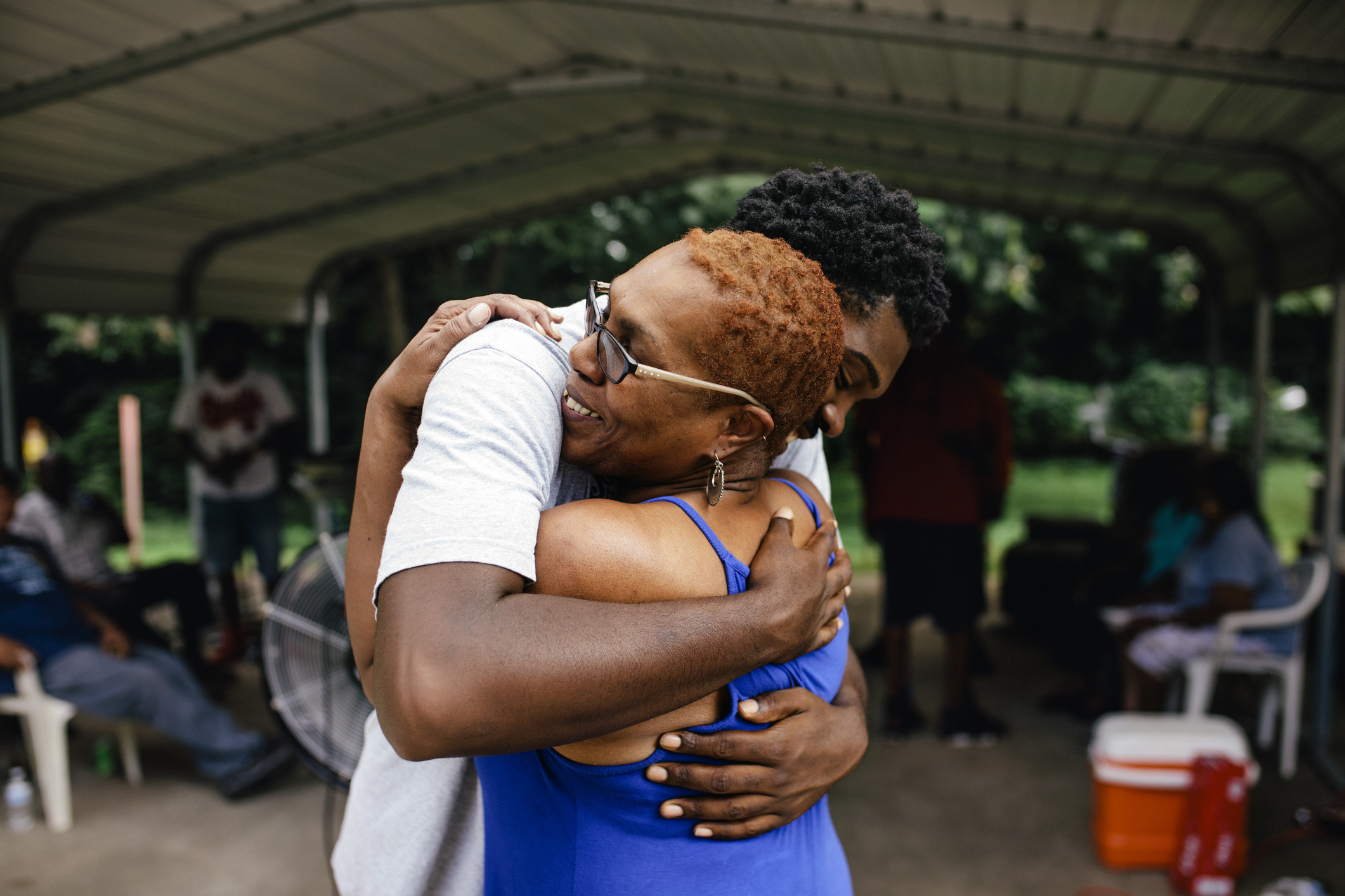 Middle aged black mother hugging her young adult son. Family outdoor cookout happening in the background.