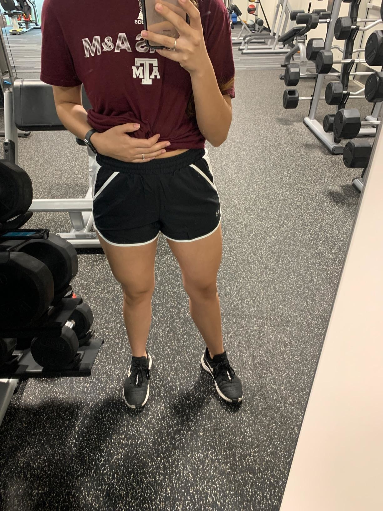 Reviewer wears black Under Armour running shorts while taking a selfie at the gym