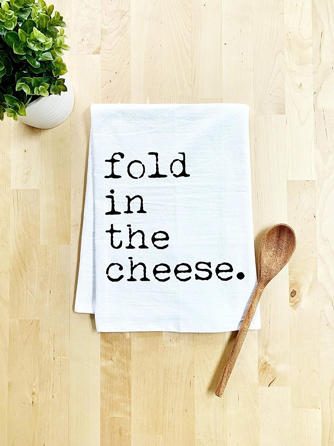 "The white dish towel with a quote from Schitt's Creek's that says ""Fold in the cheese"""