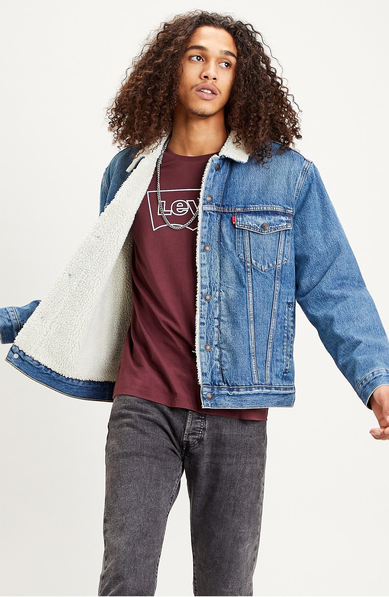 Model wearing the blue denim jacket with white faux fur in the inside and collar