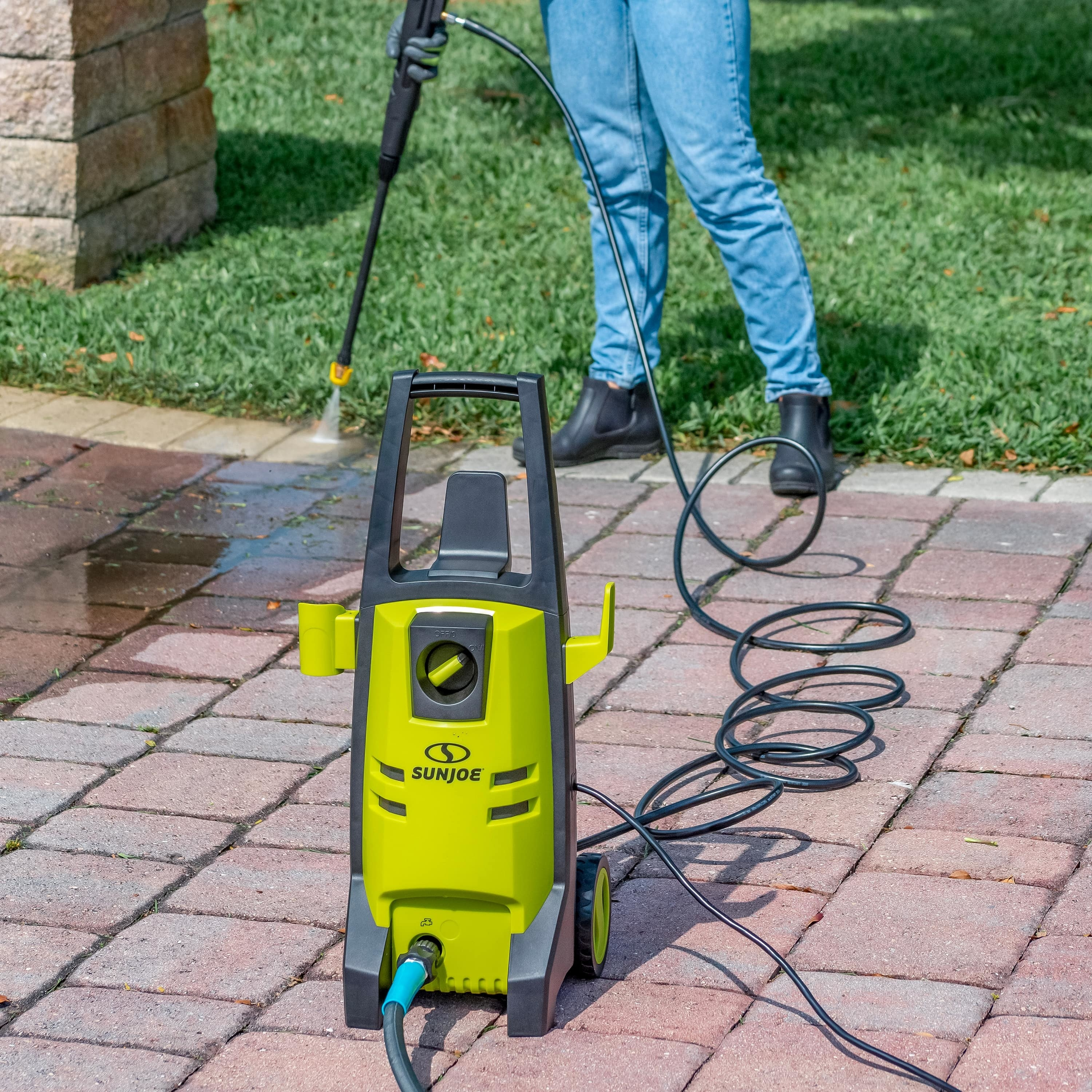 person using a sunjoe electric pressure washer to clean a driveway