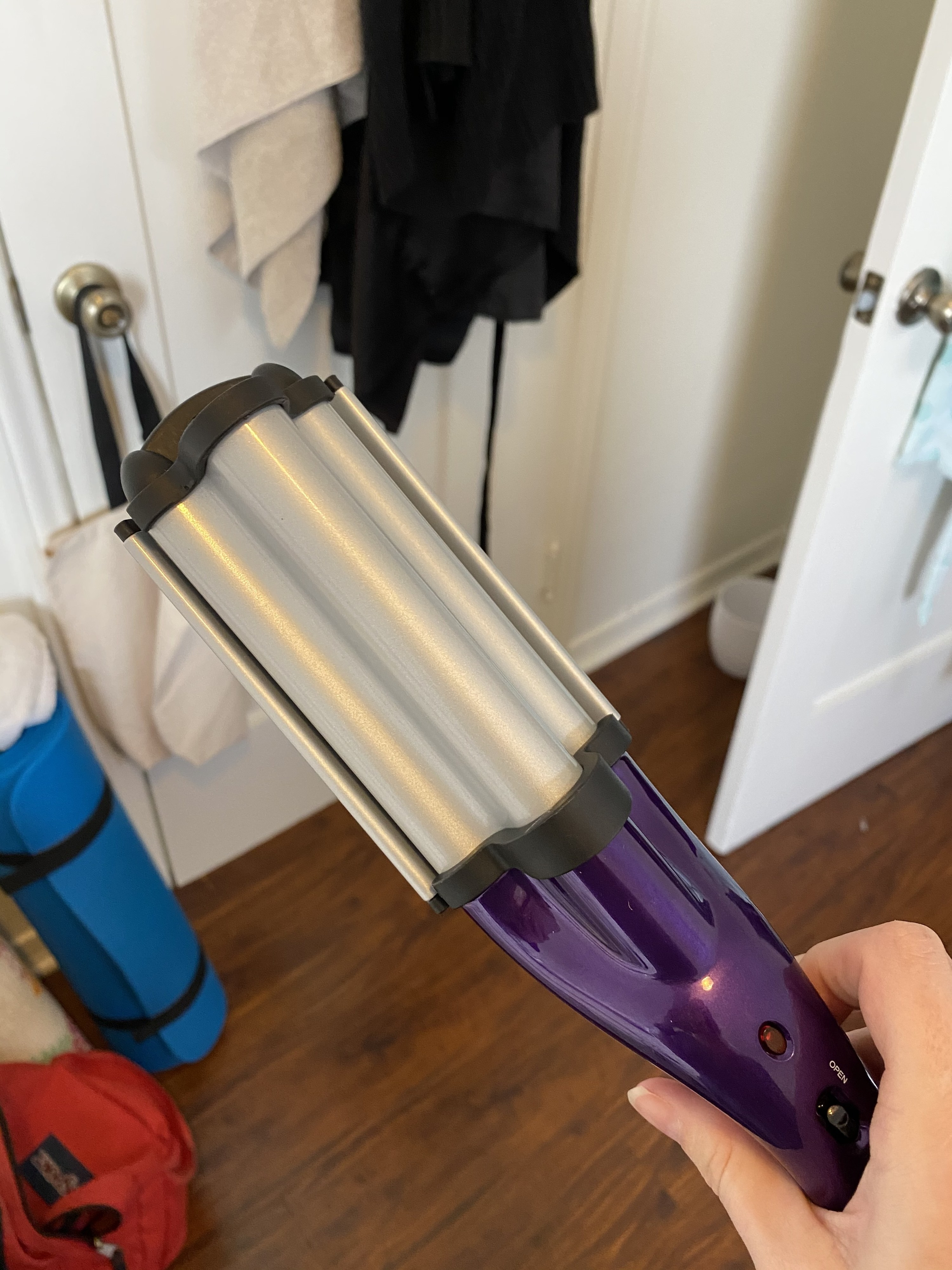 """The Bed Head waver held in my hand, with two clamps and iron plates that create an """"S"""" shape when held together. The tool is pretty proportional to my hand, and other hair tools, but I expected it to be much larger."""