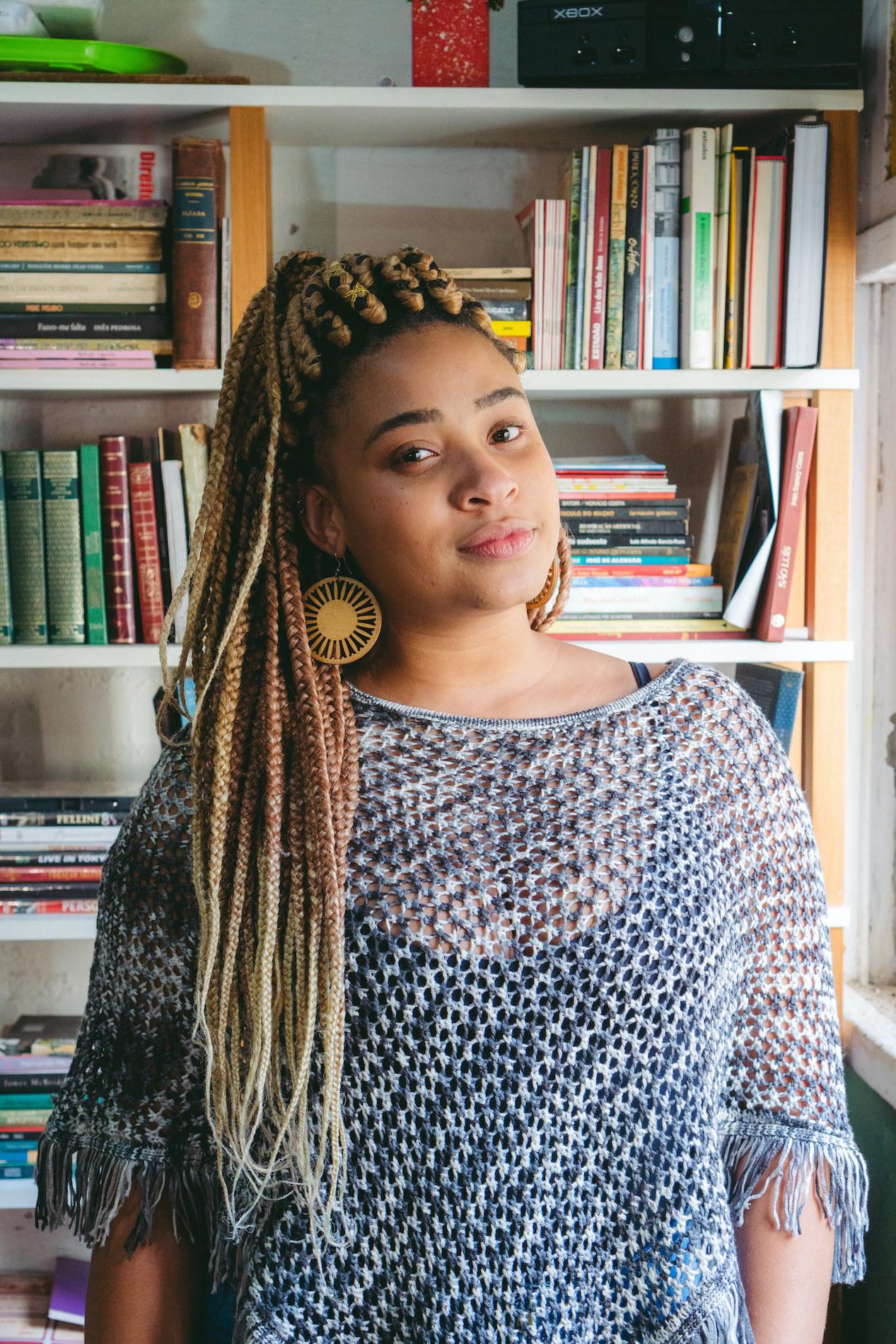 Kellen Silva na frente de estante de livros na Ocupação 9 de Julho.