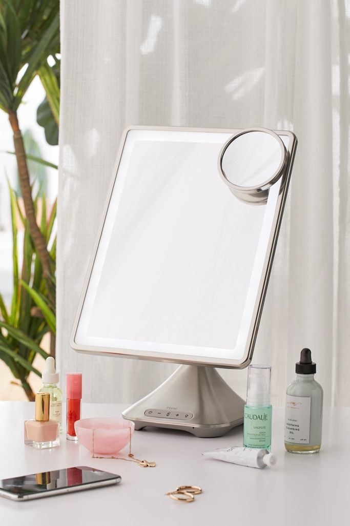 the mirror displayed on a desk with beauty products around it