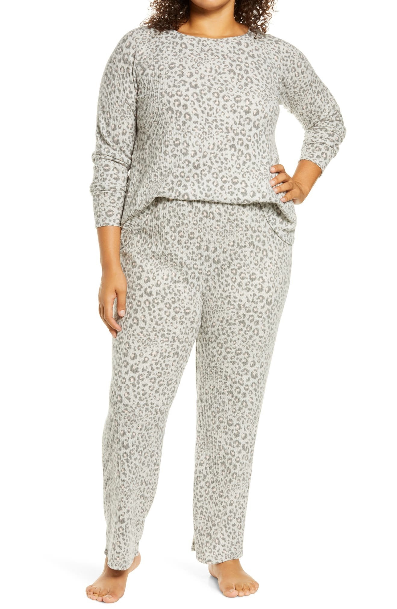 Model wearing the full-length pajama pants and long-sleeved shirt in grey with a darker grey leopard print on them