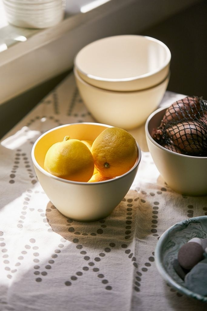 the bowls in the color yellow filled with lemons and onions