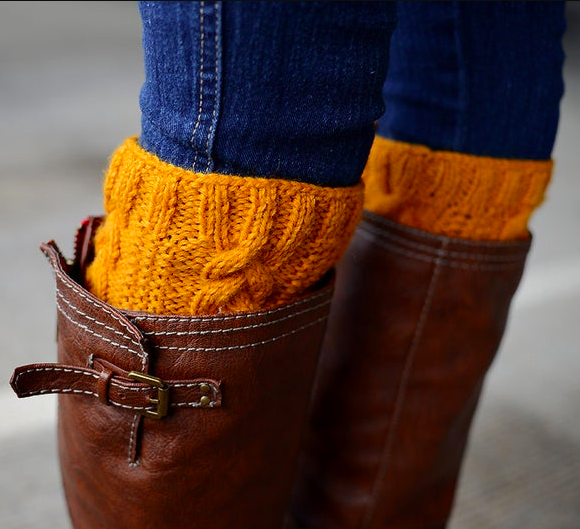 A pair of cable knit boot toppers peeking out from knee high leather boots