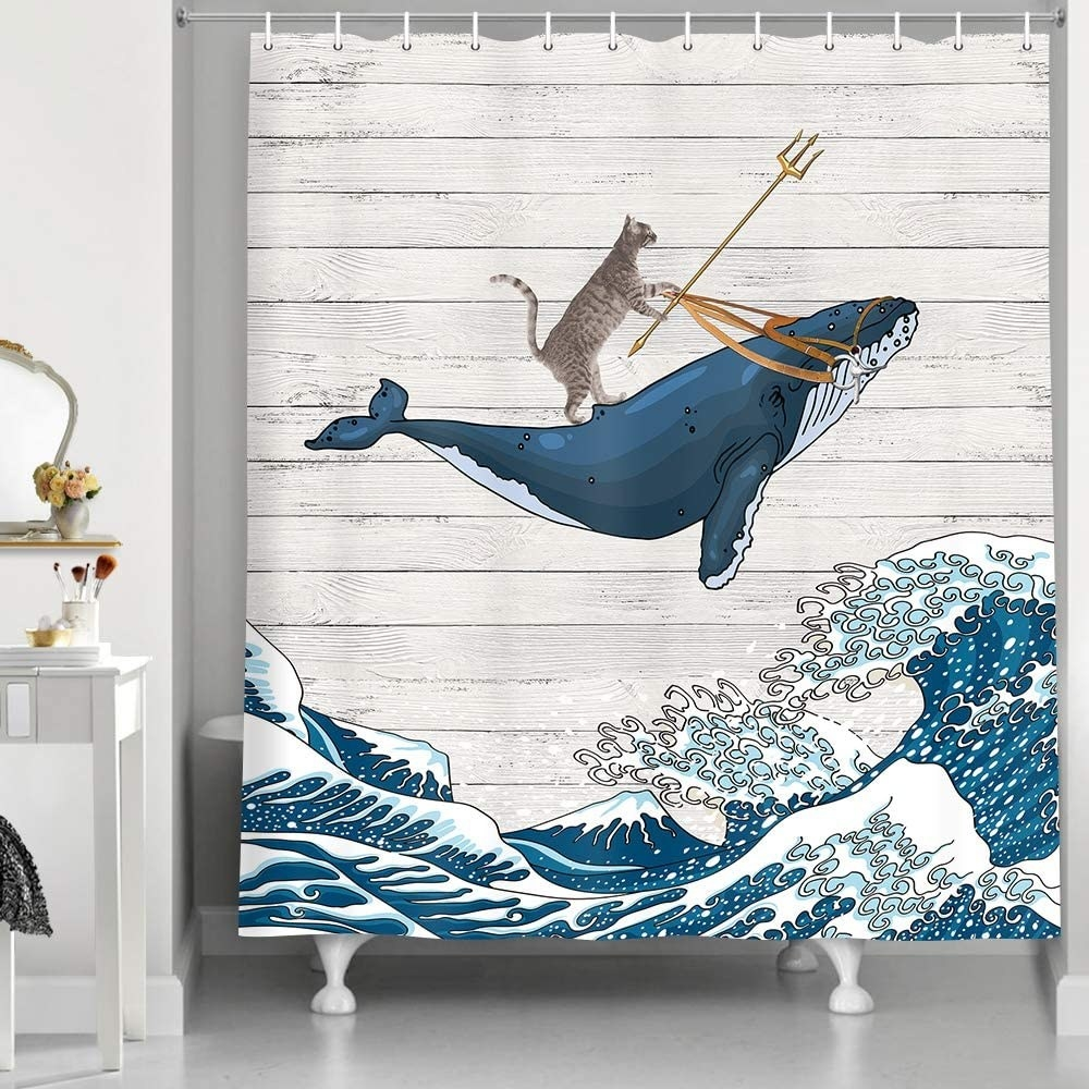 The shower curtain with an illustration of a cat riding a whale and holding a trident