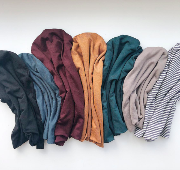 Seven slouchy toques arranged on a simple background