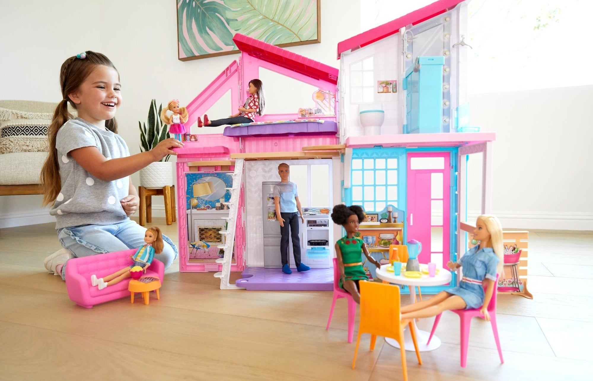 child playing with a barbie malibu house playset and their barbie dolls