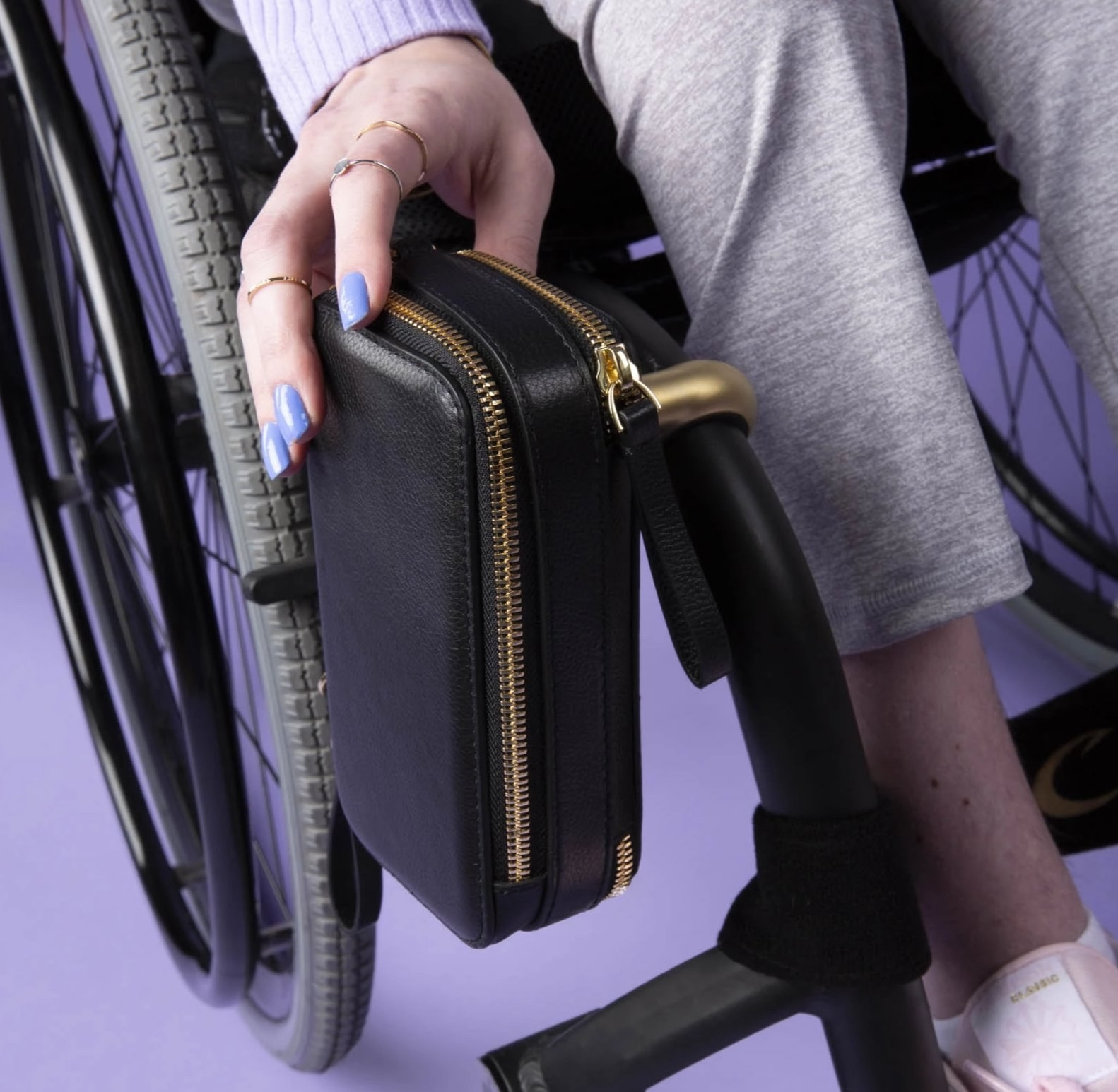 A sleek black pouch attached to a wheelchair