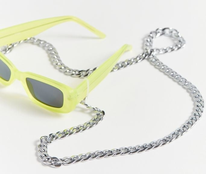 the silver sunglasses chain attached to a yellow pair of sunglasses