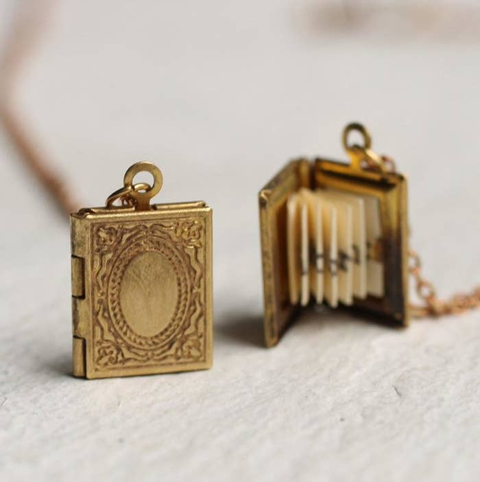 The gold tone pocket that looks like an antique book from the front and pictured with the locket open to show the pleated paper message