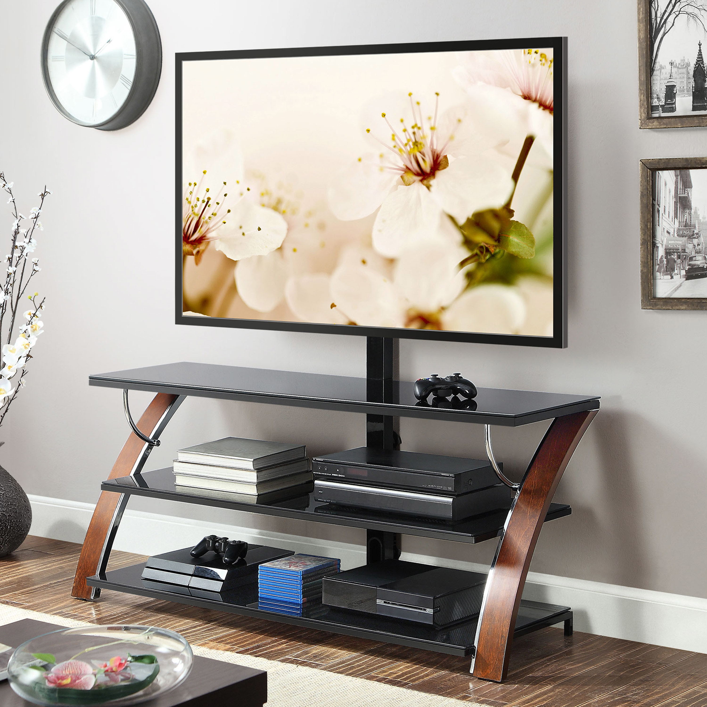 black three tier tv stand with a flat screen tv on top