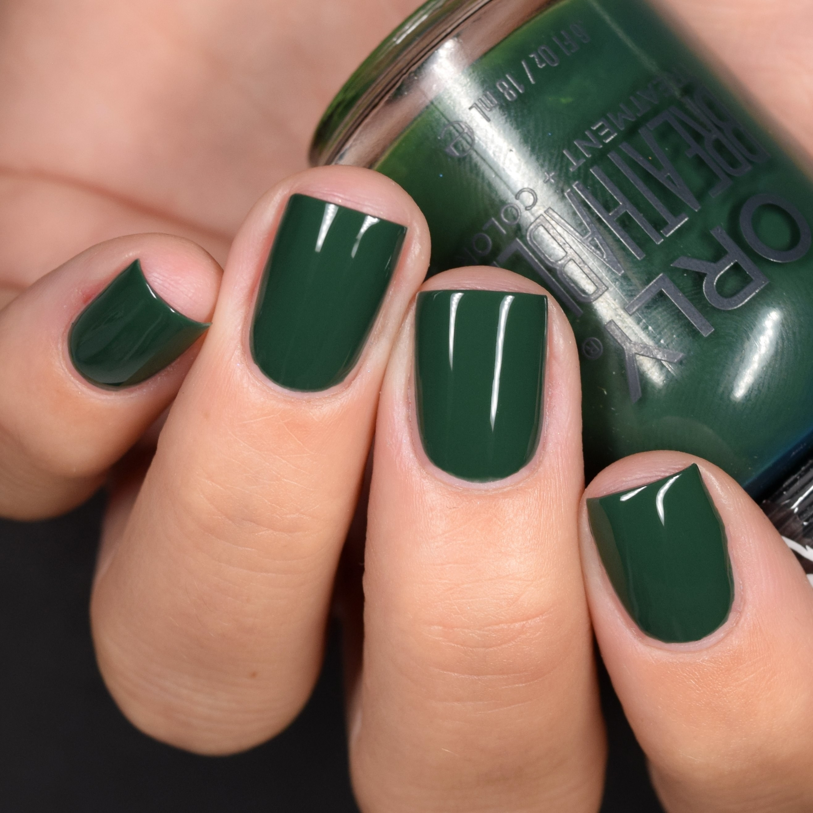 Fingers wearing dark green nail polish