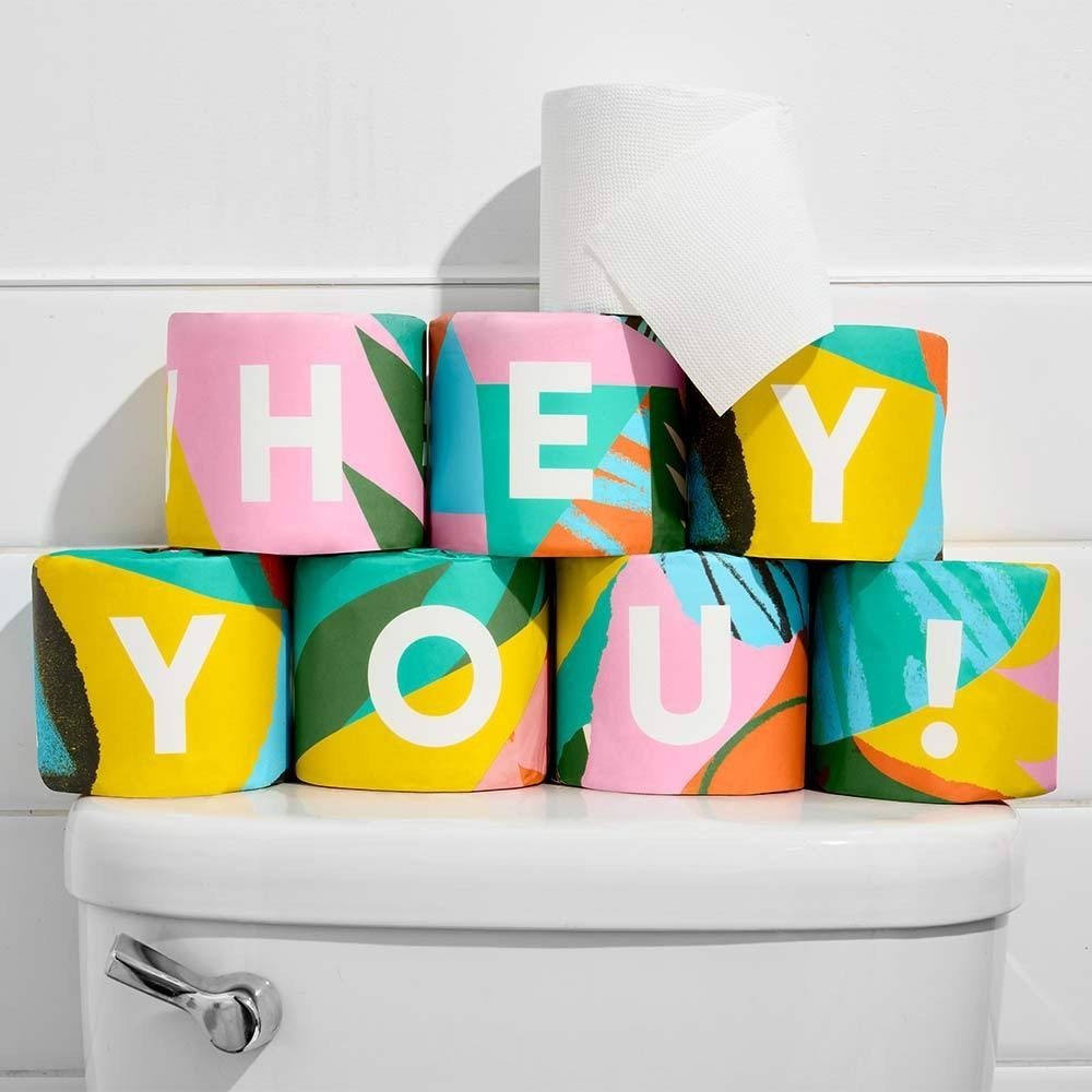 """colorfully wrapped individual toilet paper rolls that spell out """"HEY YOU!"""" on a toilet tank"""