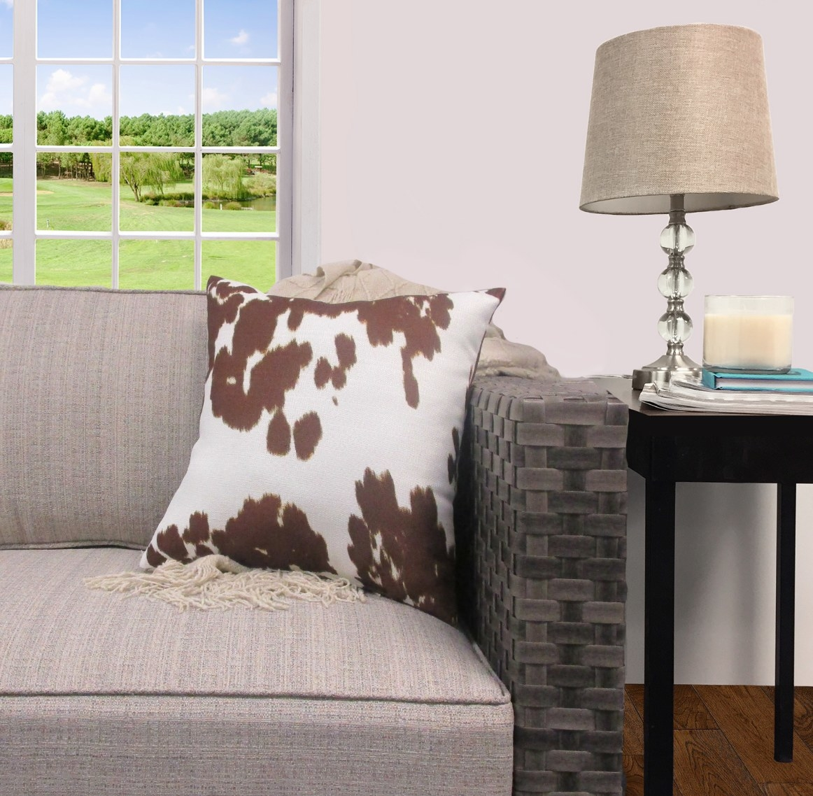 The faux cow hide throw pillow on a couch