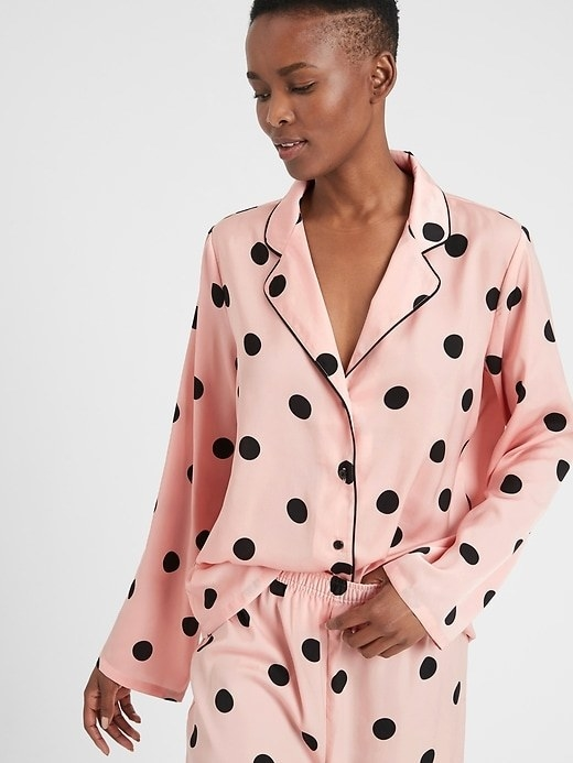 A model wearing the pajama top in pink with black dots