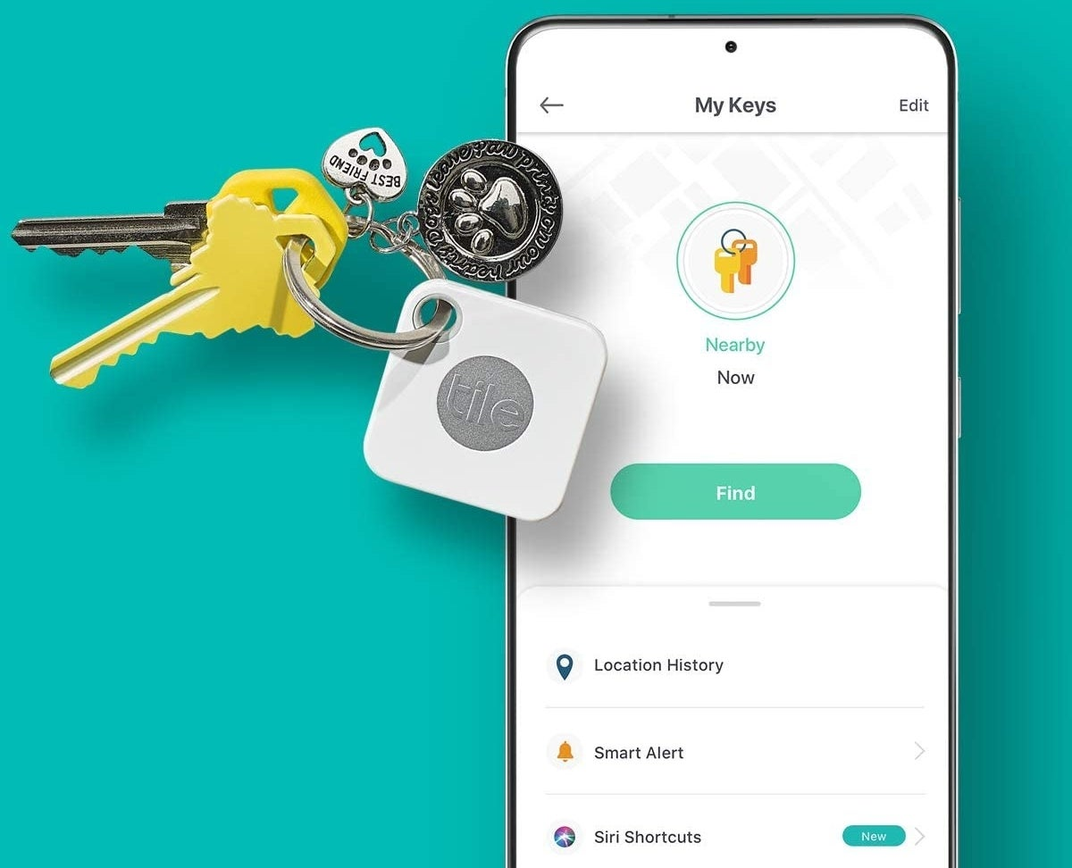 A Tile on a key ring with keys next to a phone displaying the app