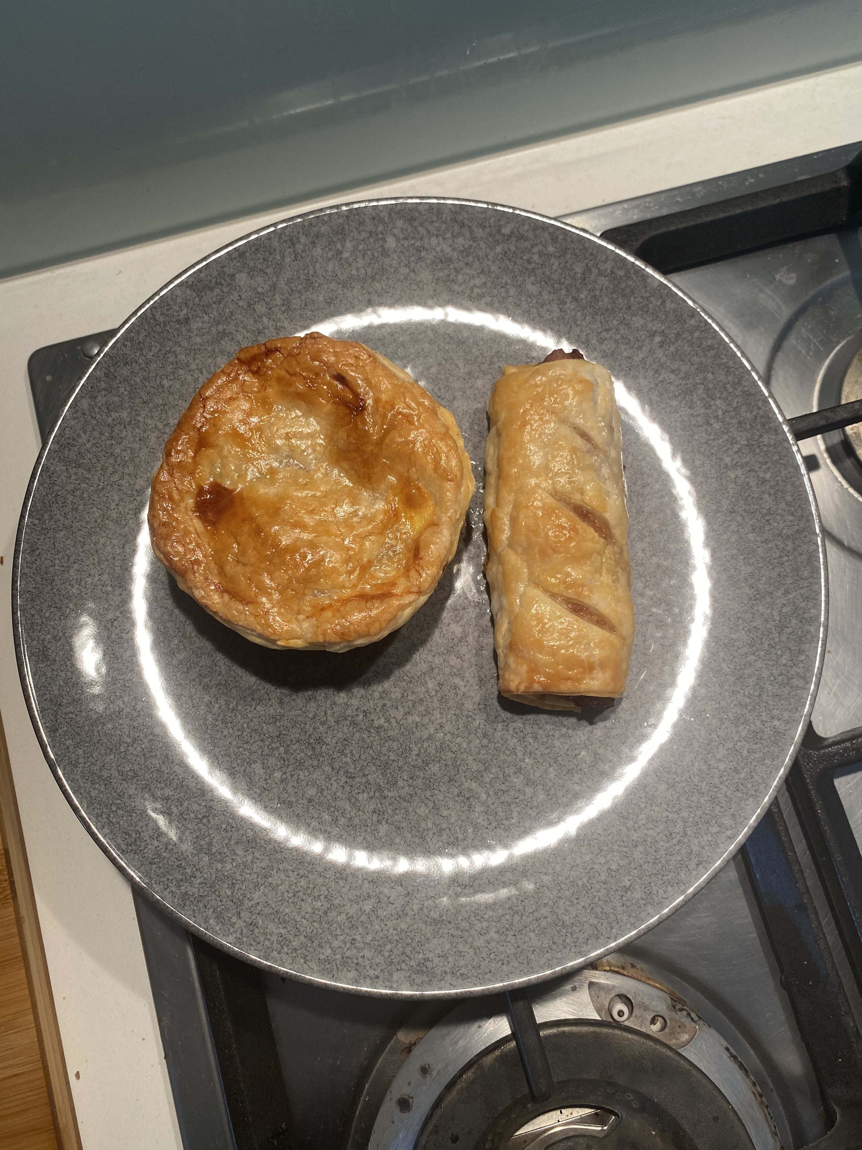 Sausage roll and pie on a plate