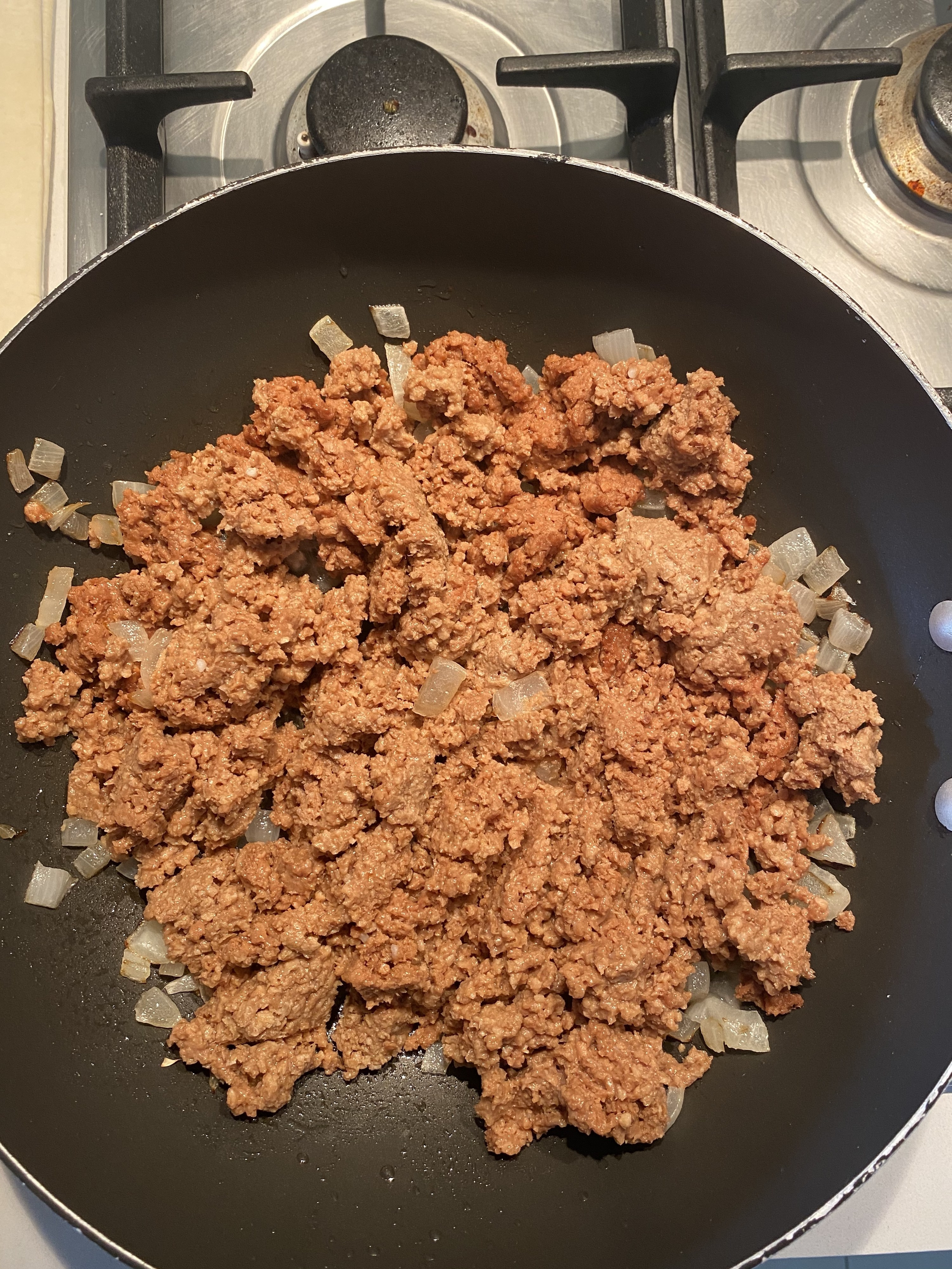 Uncooked mince in the pan with onions