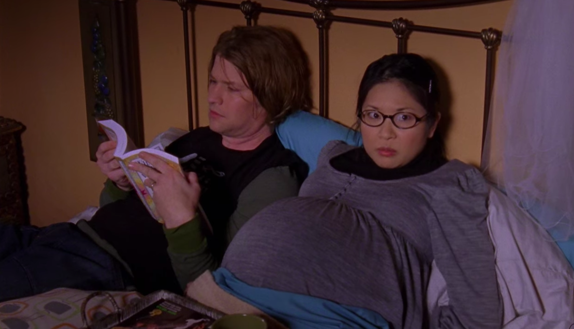 Lane pregnant with twins, lying in bed next to Zack