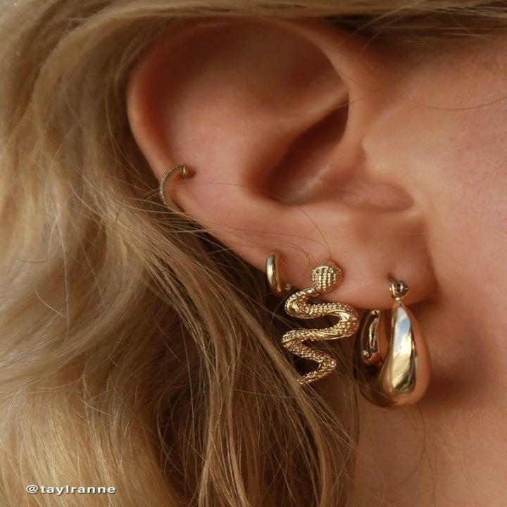 model wearing gold snake earrings