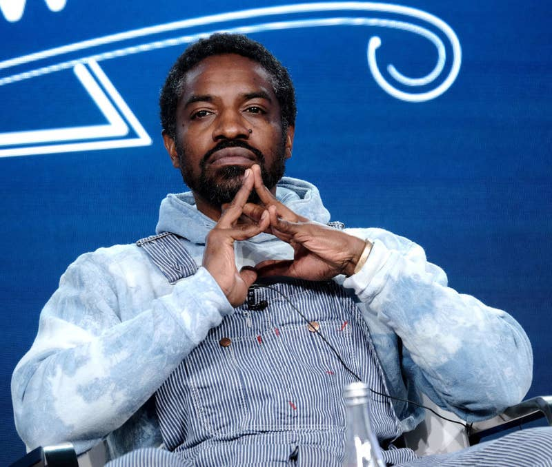 André 3000 sitting in a chair while wearing overalls, clasping his hands together while thinking pensively