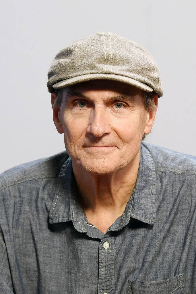 James Taylor posing for a portrait in the late 2010s while smizing and wearing a cap