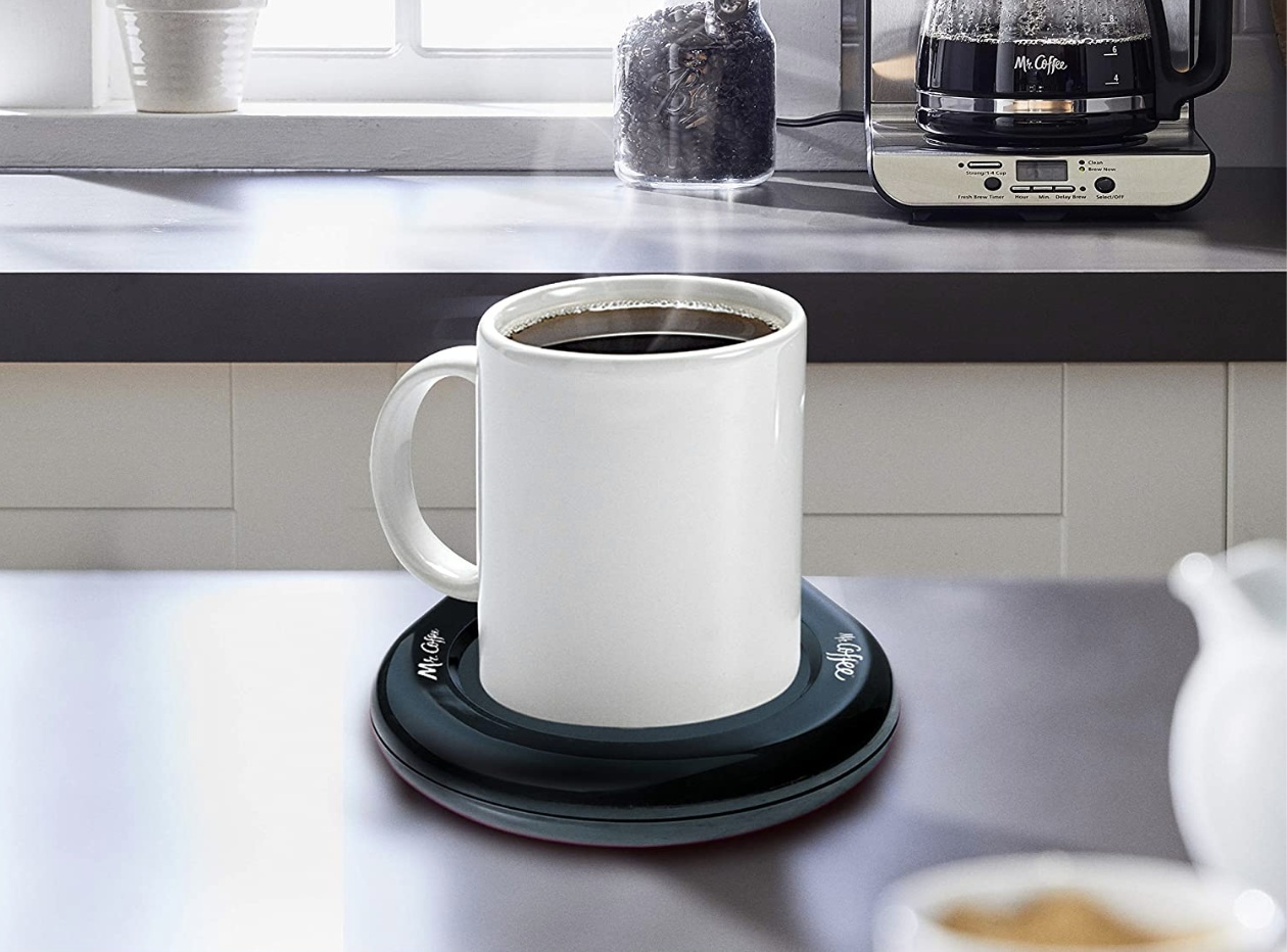 A mug of coffee on top of a black round heated small plate