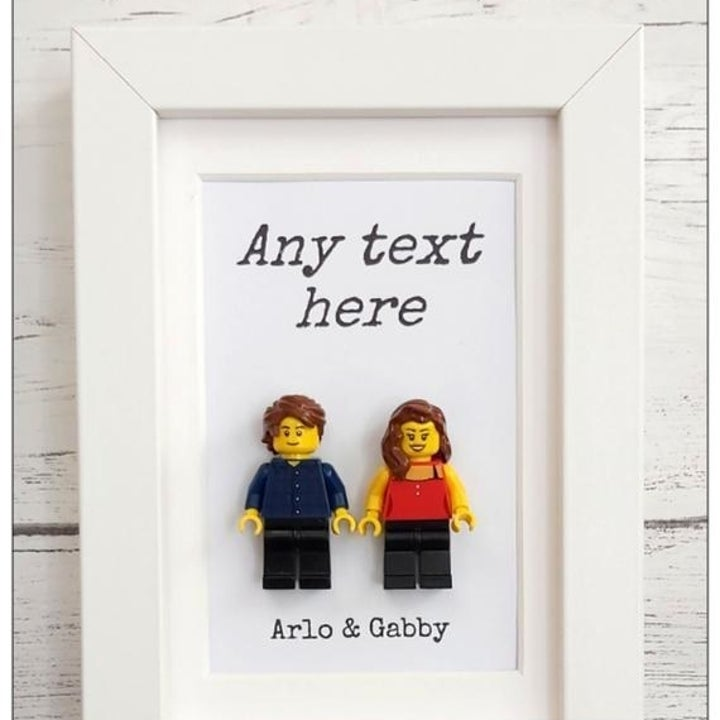 "A framed portrait of two three-dimensional Lego figures with text above them that reads ""Any text here"" and text below that reads ""Arlo & Gabby"""