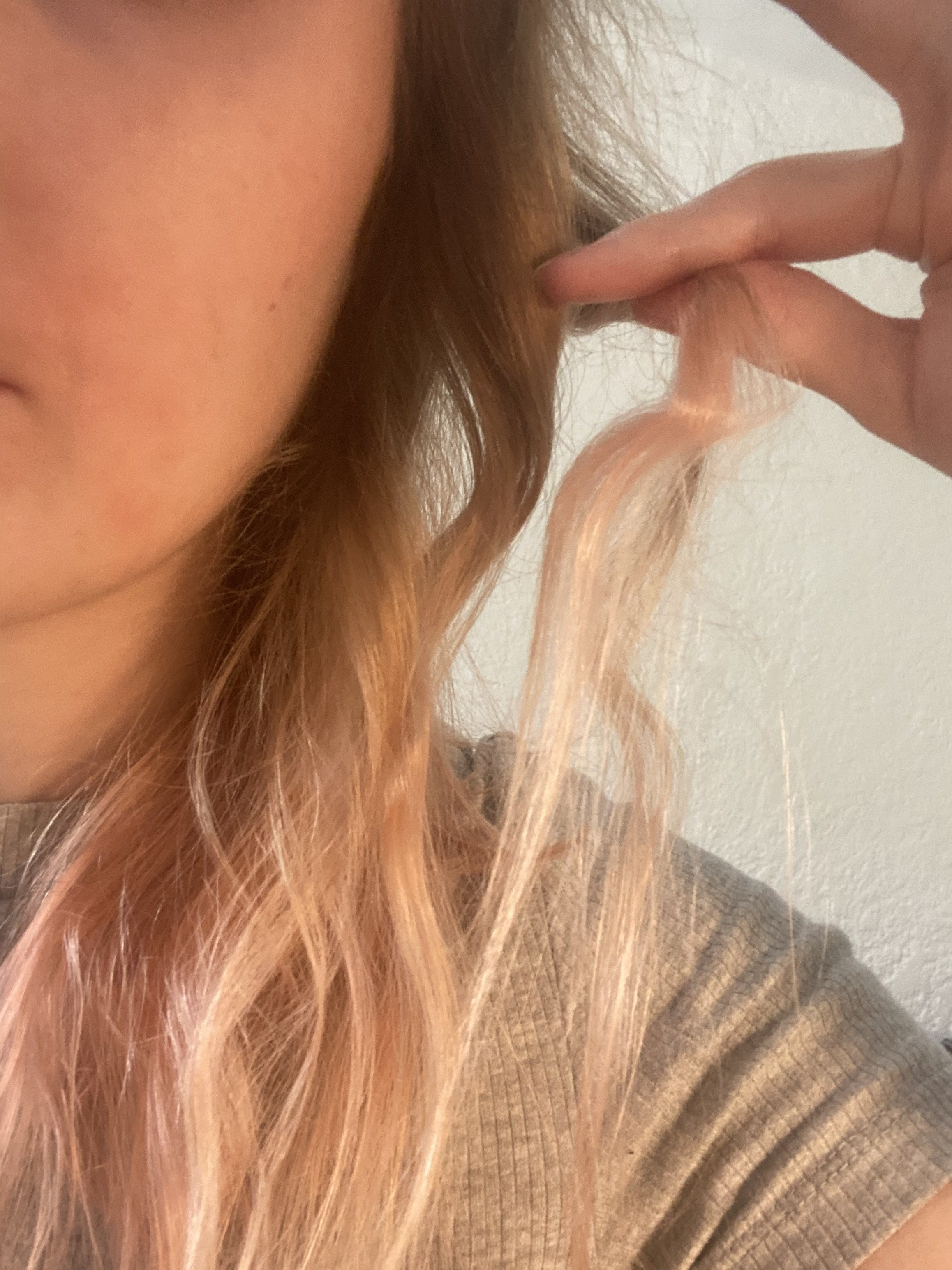 """A small section of hair between my fingers showing off a dent that nearly makes the hair look like it's in an """"L"""" shape"""