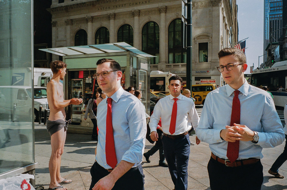 Three similar-looking men in blue shirts and red ties walking toward the camera on a Manhattan street
