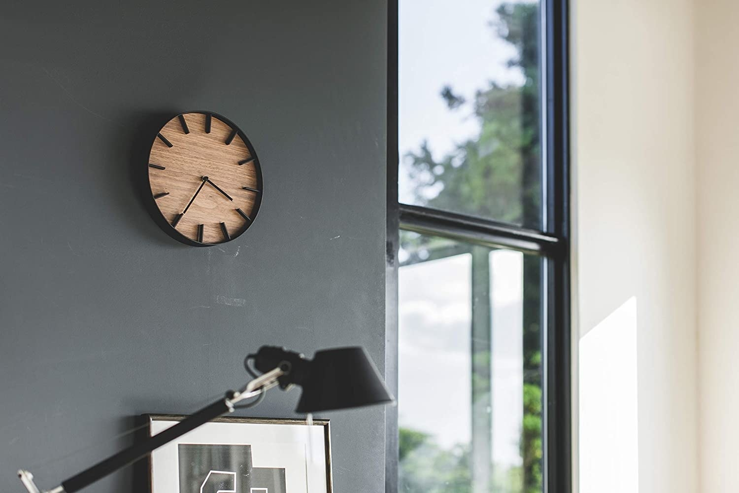 wood clock with black steel accents on an office wall