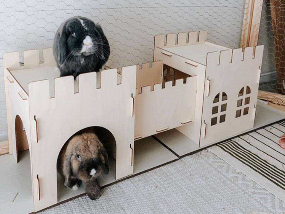 The castle, which is made of interlocking wood pieces to create two towers connected by a moat, with one bunny on top of the tower and one underneath